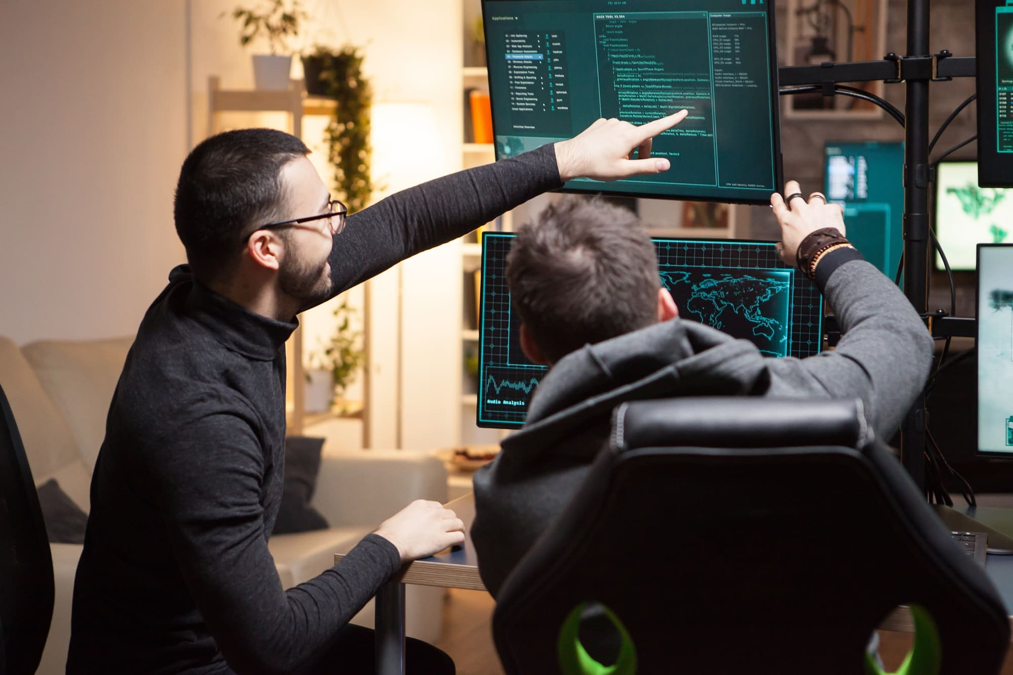 Back view of hackers pointing on computer screens