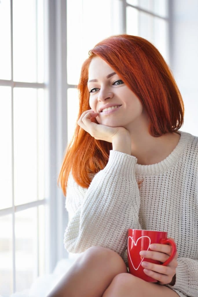 Beautiful red-haired woman near window with red mug in hands