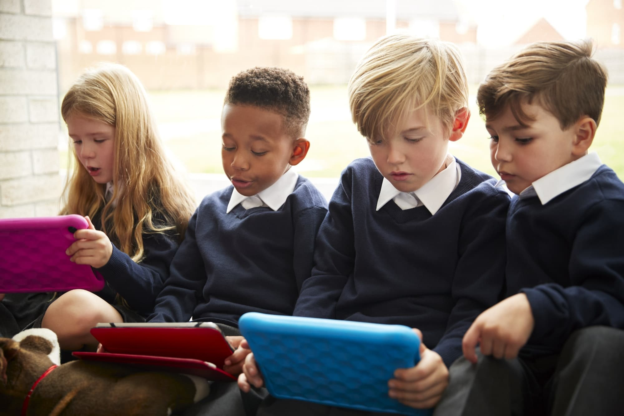 Four primary school children sitting on the floor in front of a window using tablet computers