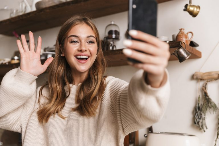 Image of happy woman taking selfie on smartphone and waving hand