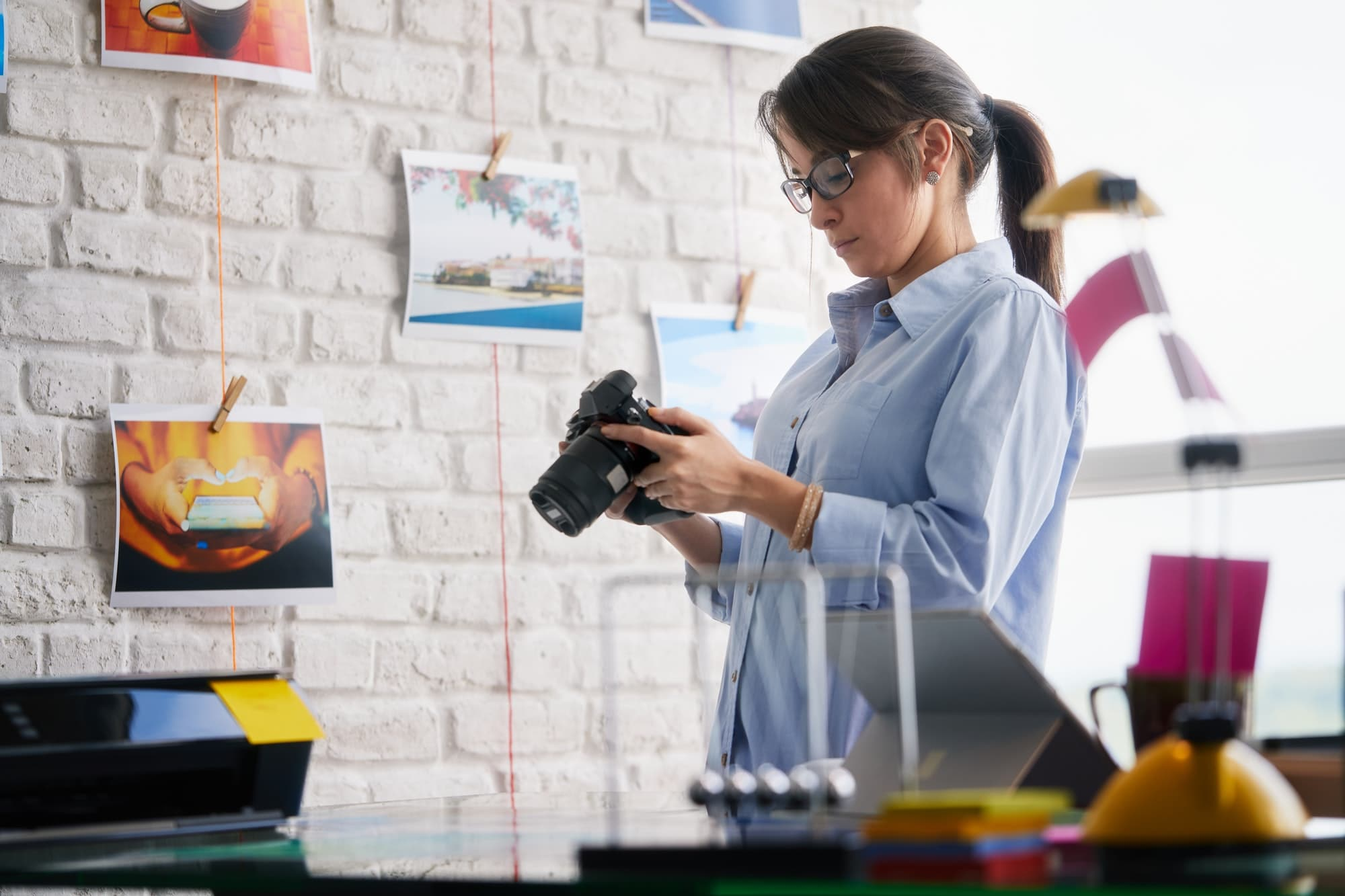 Photographer Working And Checking Digital Camera Settings In Office
