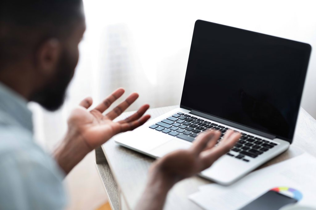 Worried african american man looking at laptop with blank screen